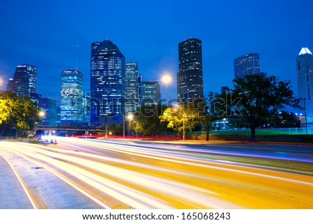 Houston Texas modern skyline at sunset twilight with traffic headlights lights trace - stock photo