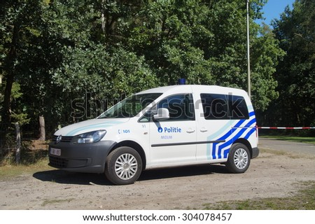 Houthalen,Belgium - August 6, 2015: Belgian Police Car (K-9 unit), Volkswagen Caddy, parking on the side of the road in front of trees. Nobody in vehicle. - stock photo