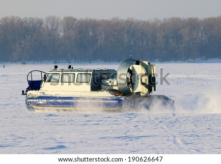 Hovercraft crossing frozen river in the sunny day - stock photo