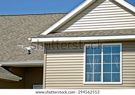 hovering drone with camera near residential home - stock photo