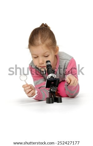 How interesting to see small objects. When I grow up, I will be a scientist. Little girl looking through a microscope. - stock photo