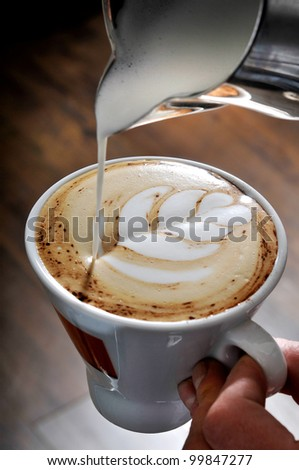 how make a flower in cappuccino coffee with milk - stock photo