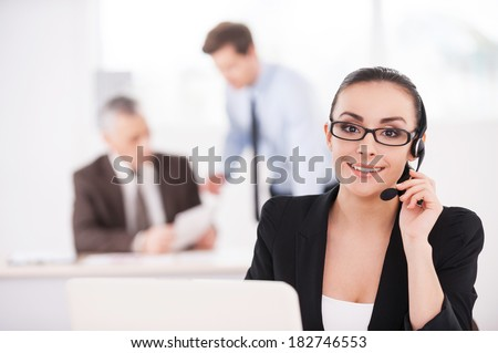 How may I help you? Beautiful young woman in formalwear adjusting her headset and smiling while people working on background  - stock photo