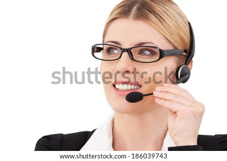 How may I help you? Confident mature customer service representative adjusting her headset and smiling while standing isolated on white - stock photo