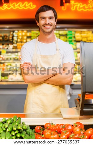 How may I help you? Handsome young cashier keeping arms crossed and smiling while standing at supermarket checkout - stock photo