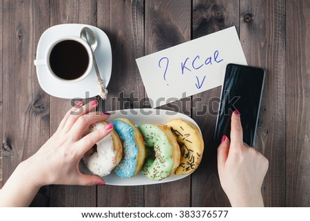 How much calories in sweet donuts, woman hold note with question - stock photo