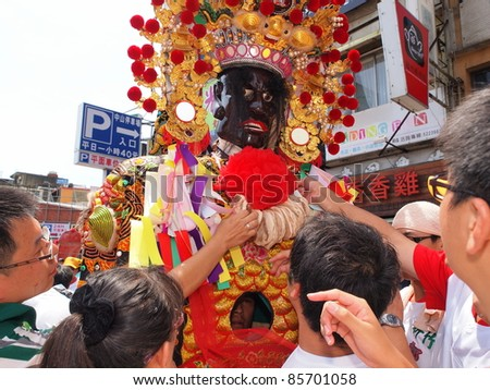 "HSINCHU,TAIWAN-AUGUST 14:People take ""peace cookies"" from a puppet in a Ghost Festival parade in Hsinchu, Taiwan on August 14, 2011.Ghost Festival is celebrated on the 15th day of the 7th lunar month. - stock photo"