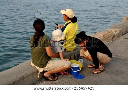 Hua Hin, Thailand - December 31, 2009:  Three women and a child fishing at the Hua Hin public fishing pier - stock photo