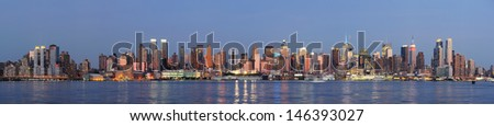 Hudson River waterfront view of New York City Manhattan after sunset with cityscape panorama and light reflection in tranquil blue tone. - stock photo