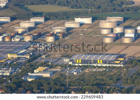 HUENXE, GERMANY - SEPTEMBER 9, 2012: Aerial view of industrial park Bucholtwelmen at sunset. The fuel depot with 52 large storage tanks is surrounded by a famous natural park. - stock photo