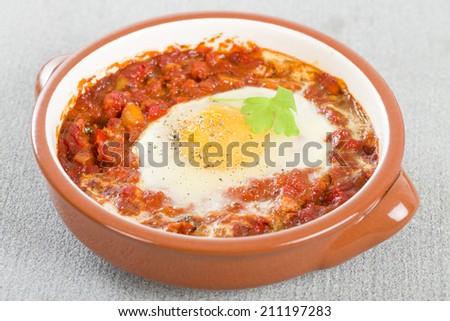 Huevos a la Flamenca (Flamenco Eggs) - Eggs poached in tomato sauce. - stock photo