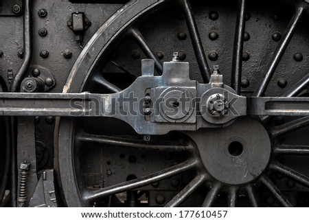 Huge black metal gear train wheel structure on the old steam engine train locomotive close up - stock photo