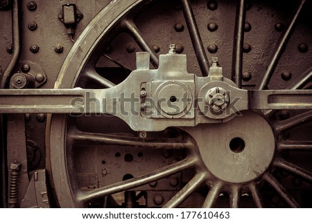 Huge black metal gear train wheel structure on the old steam engine train locomotive close up, steampunk brown colored - stock photo