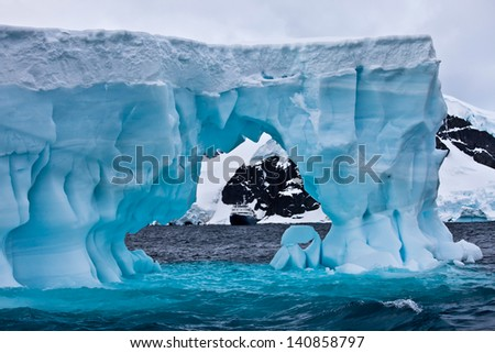 Huge blue iceberg with cruise ship in the distance, Antarctica - stock photo