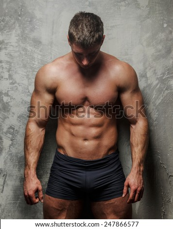 Huge bodybuileder poses showing his pumped musculed body - stock photo