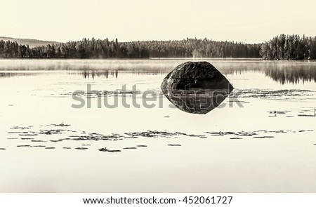 Huge boulder with a reflection in the water of the northern misty lake surrounded by pine forest. Monochrome, sepia and vintage filter. - stock photo