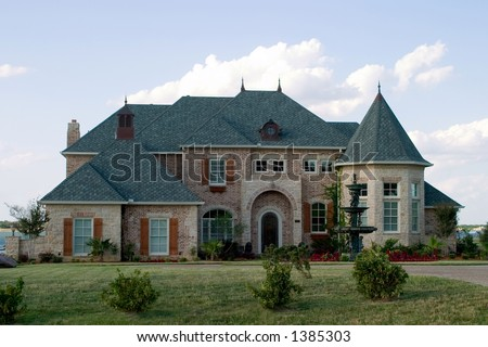 Huge brick modern French provencial style house with ornate fountain and beautiful landscaping on small lake. - stock photo