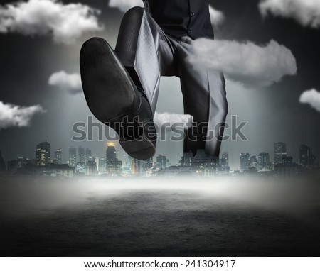 Huge businessman goes across the town - stock photo