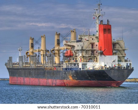 Huge cargo ship heading for port - stock photo