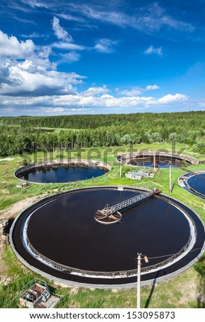 Huge circular settlers of sewage treatment plant under blue sky - stock photo
