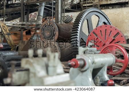 Huge cog wheel in large industrial hall - stock photo