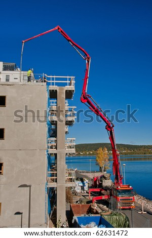 Huge concrete pump with tall arm pumping concrete on top of the building with workers - stock photo