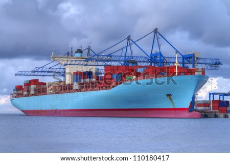 Huge container cargo ship is being unloaded - stock photo