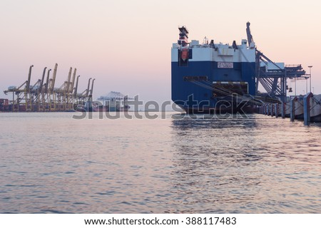Huge container cargo ship on harbor while load car into it - stock photo