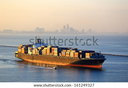 Huge container cargo ship outgoing from port at sunrise  - stock photo