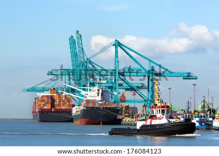 Huge container ship being unloaded with cranes in Antwerp container terminal - all recognizable logos and brands have been removed - stock photo