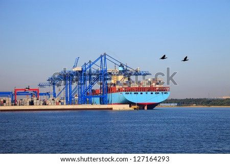 Huge Container Ship during loading in port terminal at Gdansk, Poland. - stock photo