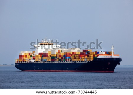 Huge container ship passing - all brand names removed from every container - stock photo