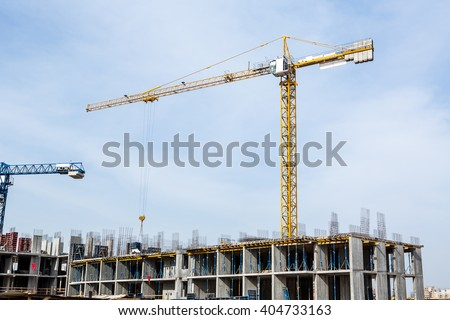 Huge crane and construction plant. Big construction crane and the building against the sky background. Tower Crane in Construction site. - stock photo