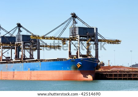 Huge cranes unloading ore from a bulk carrier - stock photo