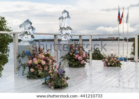 Huge crystal sculptures stand on  a porch behind big rose bouquets - stock photo