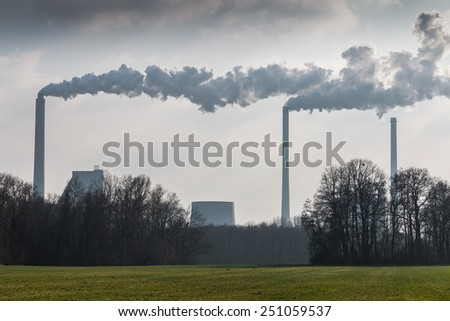 Huge factory chimneys polluting the air - stock photo
