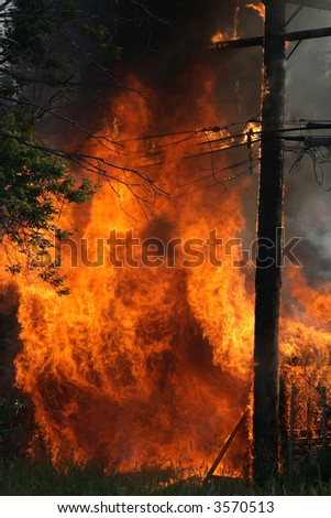 Huge garage fire catches an electrical pole on fire - stock photo