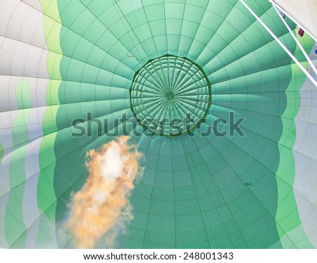 Huge gas flame heating the air in a green hot air balloon - stock photo
