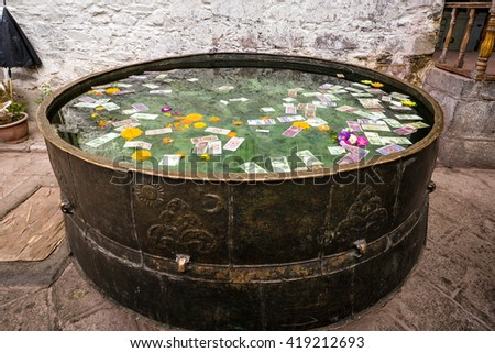 Huge holy water tank with money in Jokhang temple's courtyard. - stock photo