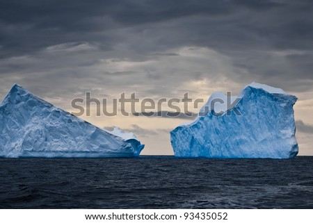 Huge icebergs in Antarctica, dark sky - stock photo