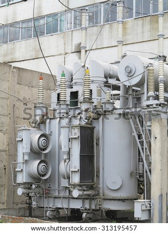 Huge industrial high-voltage substation power transformer on rails at power plant - stock photo