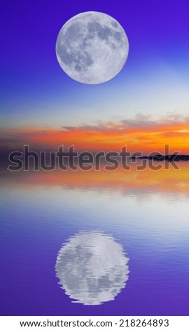 huge moon in a blue and orange sky reflected in the water - stock photo