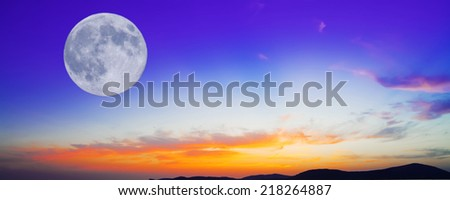huge moon  in an orange and blue sunset - stock photo