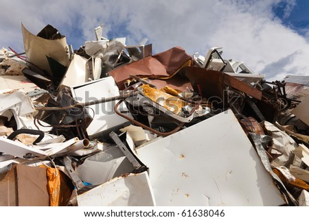 Huge pile of scrap metal with cloudy sky background - stock photo