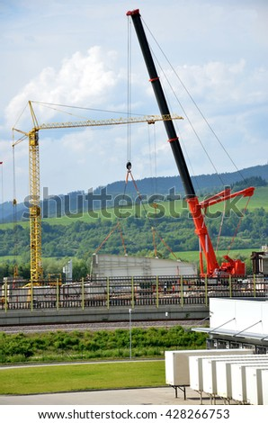 Huge red crane and yellow tower crane and some workers on construction site during highway building process. Logistics center in foreground.   - stock photo