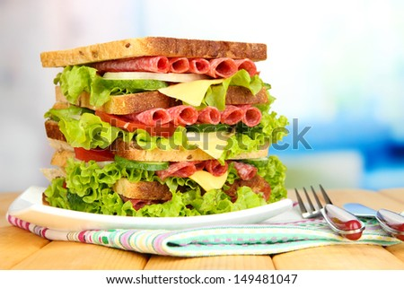 Huge sandwich on wooden table, on light background - stock photo
