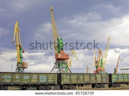 huge seaport cranes in front of railway with wagons - stock photo