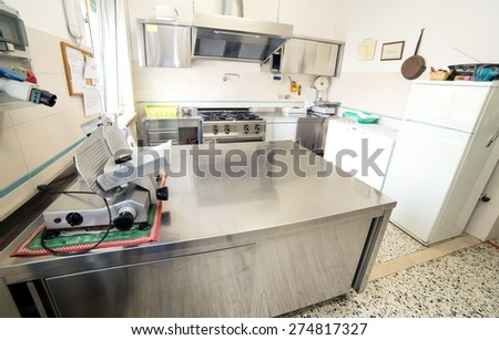huge stainless steel kitchen with gas stove and an industrial meat slicer - stock photo