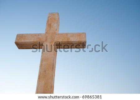 Huge stone cross monument against evening sky - stock photo
