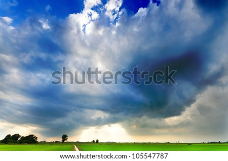 Huge storm approaching at sunset - stock photo